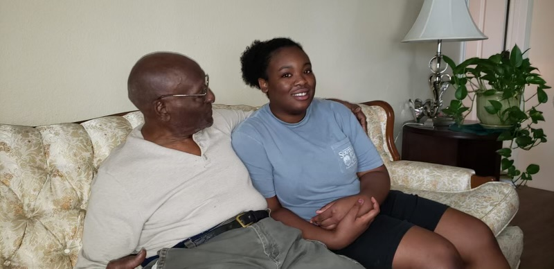 Senior Margaret Mutoke lounges on a couch with her deceased grandfather